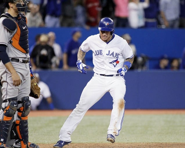 Jul 26, 2013; Toronto, Ontario, CAN; Toronto Blue Jays third baseman Brett Lawrie (13) comes home on a grand slam home run by  designated hitter Edwin Encarnacion (not pictured) in the seventh inning against the Houston Astros at the Rogers Centre. Mandatory Credit: John E. Sokolowski-USA TODAY Sports