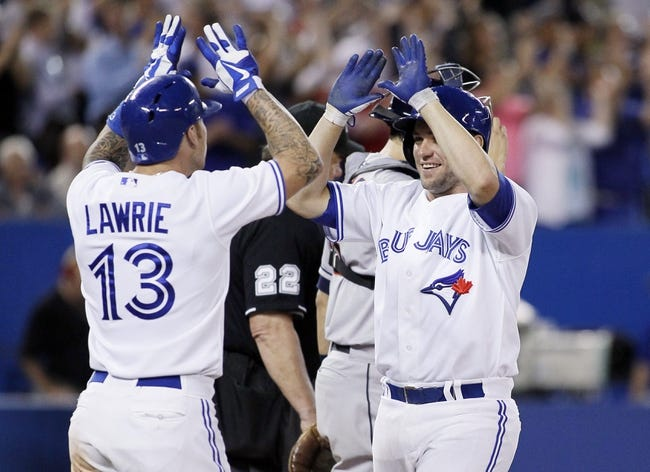 Jul 26, 2013; Toronto, Ontario, CAN; Toronto Blue Jays third baseman Brett Lawrie (13) and catcher Josh Thole (30) score on a grand slam home run by  designated hitter Edwin Encarnacion (not pictured) in the seventh inning against the Houston Astros at the Rogers Centre. Mandatory Credit: John E. Sokolowski-USA TODAY Sports