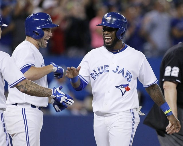 Jul 26, 2013; Toronto, Ontario, CAN; Toronto Blue Jays catcher Josh Thole (left) and shortstop Jose Reyes (7) react after scoring on a grand slam home run by  designated hitter Edwin Encarnacion (not pictured) in the seventh inning against the Houston Astros at the Rogers Centre. Mandatory Credit: John E. Sokolowski-USA TODAY Sports