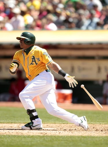 Jul 28, 2013; Oakland, CA, USA; Oakland Athletics outfielder Yoenis Cespedes (52) hits a two-run double against the Los Angeles Angels in the third inning at O.co Coliseum. Mandatory Credit: Cary Edmondson-USA TODAY Sports