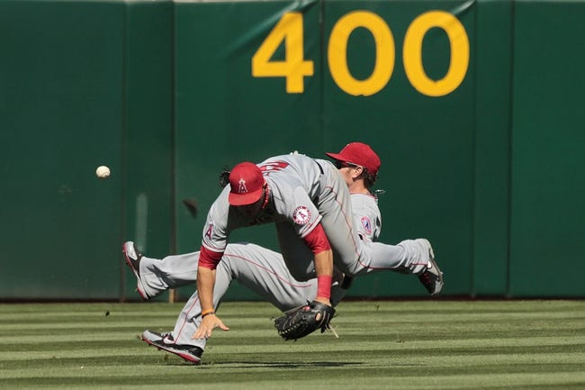 Jul 28, 2013; Oakland, CA, USA; Los Angeles Angels outfielder Mike Trout (27) and outfielder Josh Hamilton (32) collide after failing to make a catch on a double by Oakland Athletics catcher Stephen Vogt (not pictured) in the sixth inning at O.co Coliseum. Mandatory Credit: Cary Edmondson-USA TODAY Sports