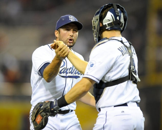 Jul 30, 2013; San Diego, CA, USA; San Diego Padres relief pitcher Huston Street (16) celebrates with catcher Nick Hundley (4) after a win against the Cincinnati Reds at Petco Park. The Padres won 4-2. Mandatory Credit: Christopher Hanewinckel-USA TODAY Sports