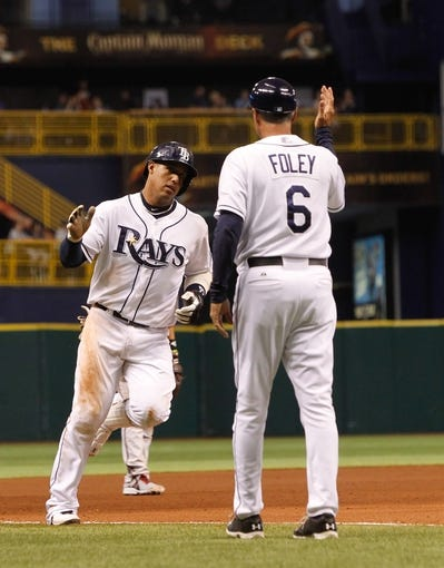 Jul 30, 2013; St. Petersburg, FL, USA; Tampa Bay Rays shortstop Yunel Escobar (11) is congratulated by third base coach Tom Foley (6) as he runs around the bases after he hit a solo home run during the fourth inning against the Arizona Diamondbacks at Tropicana Field. Tampa Bay Rays defeated the Arizona Diamondbacks 5-2. Mandatory Credit: Kim Klement-USA TODAY Sports