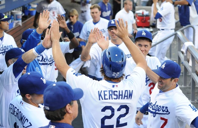 Aug 11, 2013; Los Angeles, CA, USA;  Los Angeles Dodgers starting pitcher Clayton Kershaw (22) is met in the dugout after scoring a run in the third inning against the Tampa Bay Rays at Dodger Stadium. Mandatory Credit: Jayne Kamin-Oncea-USA TODAY Sports