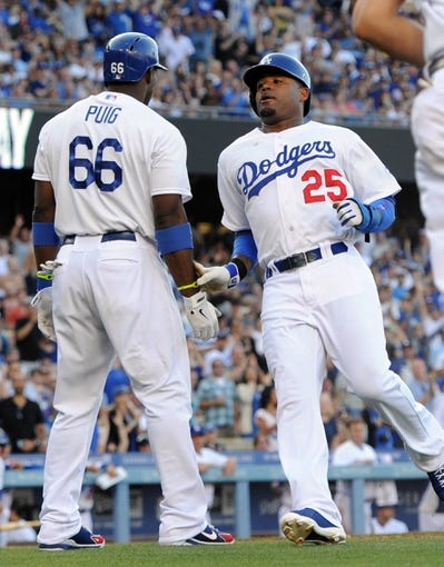Aug 11, 2013; Los Angeles, CA, USA;   Los Angeles Dodgers left fielder Carl Crawford (25) goes past right fielder Yasiel Puig (66) after scoring a run in the third inning of the game against the Tampa Bay Rays at Dodger Stadium. Mandatory Credit: Jayne Kamin-Oncea-USA TODAY Sports
