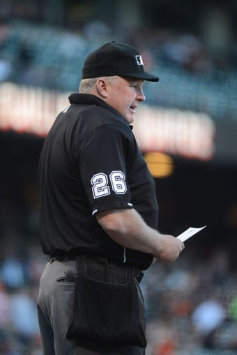 July 9, 2013; San Francisco, CA, USA; MLB umpire Bill Miller (26) looks over the lineup cards before the game between the San Francisco Giants and the New York Mets at AT&T Park. The Mets defeated the Giants 10-6. Mandatory Credit: Kyle Terada-USA TODAY Sports