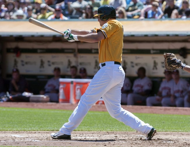 Aug 15, 2013; Oakland, CA, USA; Oakland Athletics first baseman Nate Freiman (7) hits an rbi double against the Houston Astros during the first inning at O.Co Coliseum. Mandatory Credit: Ed Szczepanski-USA TODAY Sports