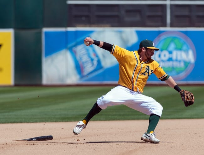 Aug 15, 2013; Oakland, CA, USA; Oakland Athletics second baseman Eric Sogard (28) is knocked down by a broken bat while fielding a ball during the seventh inning at O.Co Coliseum. The Oakland Athletics defeated the Houston Astros 5-0. Mandatory Credit: Ed Szczepanski-USA TODAY Sports