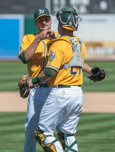 Aug 15, 2013; Oakland, CA, USA; Oakland Athletics relief pitcher Dan Otero (61) and catcher Stephen Vogt (21) bump fists after defeating the Houston Astros 5-0 at O.Co Coliseum. Mandatory Credit: Ed Szczepanski-USA TODAY Sports