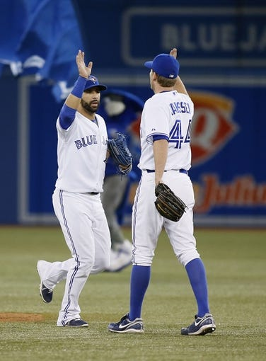 Aug 15, 2013; Toronto, Ontario, CAN; Toronto Blue Jays right fielder Jose Bautista (19) congratulates relief pitcher Casey Janssen (44) after a win against the Boston Red Sox at the Rogers Centre. Toronto defeated Boston 2-1. Mandatory Credit: John E. Sokolowski-USA TODAY Sports