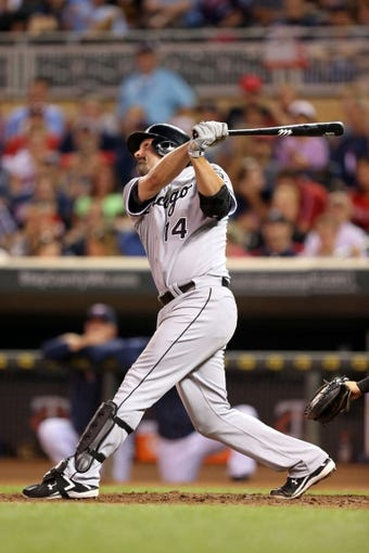 Aug 15, 2013; Minneapolis, MN, USA; Chicago White Sox first baseman Paul Konerko (14) hits a single in the sixth inning against the Minnesota Twins at Target Field. Mandatory Credit: Jesse Johnson-USA TODAY Sports