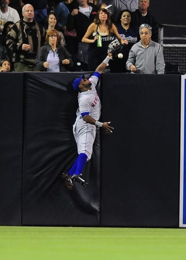 Aug 15, 2013; San Diego, CA, USA; New York Mets left fielder Eric Young Jr. (22) tries to make a catch at the wall during the third inning against the San Diego Padres at Petco Park. The play was reviewed and ruled a triple. Mandatory Credit: Christopher Hanewinckel-USA TODAY Sports
