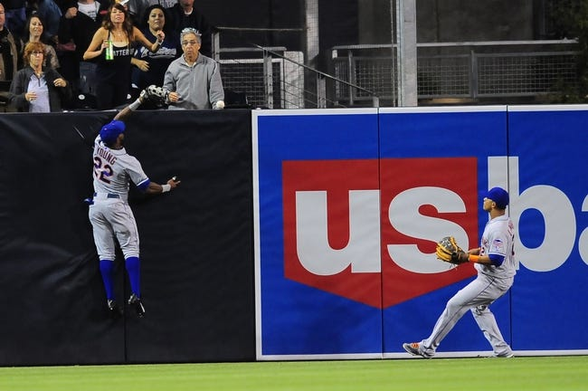 Aug 15, 2013; San Diego, CA, USA; New York Mets left fielder Eric Young Jr. (22) tries to make a catch at the wall as center fielder Juan Lagares (12) looks on during the third inning against the San Diego Padres at Petco Park. The play was reviewed and ruled a triple. Mandatory Credit: Christopher Hanewinckel-USA TODAY Sports