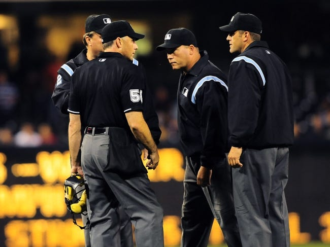 Aug 15, 2013; San Diego, CA, USA; Umpires meet on the field to discuss a play during the third inning against the New York Mets at Petco Park. Mandatory Credit: Christopher Hanewinckel-USA TODAY Sports