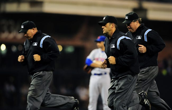 Aug 15, 2013; San Diego, CA, USA; Umpires run off the field to review a call during the third inning against the New York Mets at Petco Park. Mandatory Credit: Christopher Hanewinckel-USA TODAY Sports
