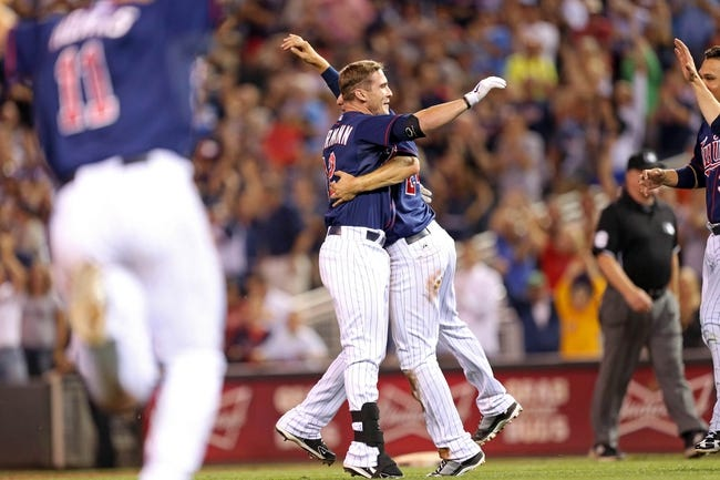 Aug 15, 2013; Minneapolis, MN, USA; Minnesota Twins pinch runner Chris Herrmann (12) celebrates with third baseman Trevor Plouffe (24) after hitting a game winning single in the ninth inning against the Chicago White Sox at Target Field. The Twins won 4-3. Mandatory Credit: Jesse Johnson-USA TODAY Sports