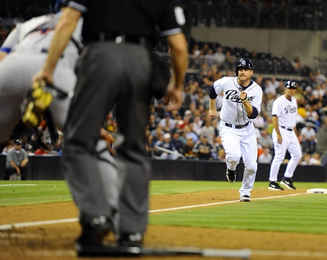 Aug 15, 2013; San Diego, CA, USA; San Diego Padres third baseman Chase Headley (7) scores on a sacrifice fly out during the fourth inning against the New York Mets at Petco Park. Mandatory Credit: Christopher Hanewinckel-USA TODAY Sports