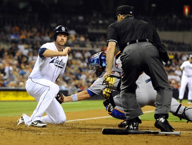 Aug 15, 2013; San Diego, CA, USA; San Diego Padres third baseman Chase Headley (7) scores ahead of the tag by New York Mets catcher John Buck (44) during the fourth inning at Petco Park. Mandatory Credit: Christopher Hanewinckel-USA TODAY Sports