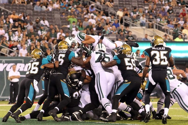Aug 17, 2013; East Rutherford, NJ, USA; New York Jets running back Kahlil Bell (24) dives over the pile just short of a touchdown during the third quarter of a preseason game at MetLife Stadium. The Jets defeated the Jaguars 37-13. Mandatory Credit: Brad Penner-USA TODAY Sports
