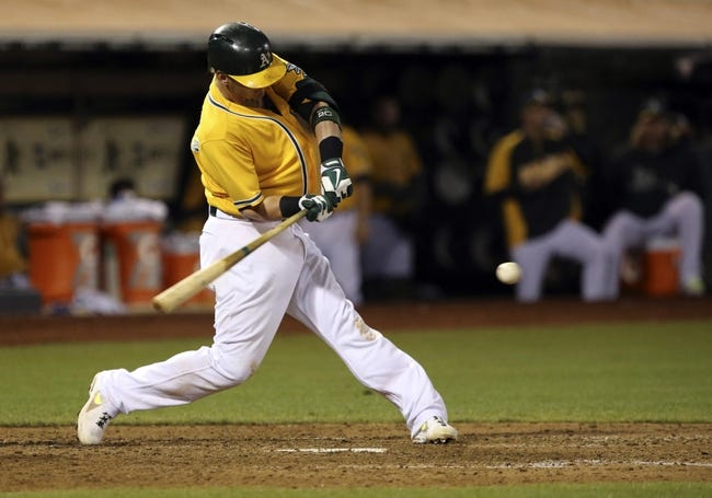 Aug 17, 2013; Oakland, CA, USA; Oakland Athletics third baseman Josh Donaldson (20) hits a single against the Cleveland Indians during the eighth inning at O.co Coliseum. Mandatory Credit: Kelley L Cox-USA TODAY Sports