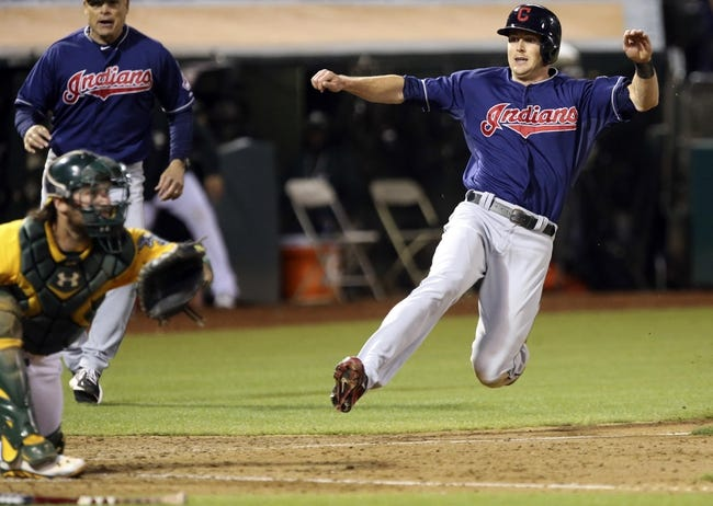 Aug 17, 2013; Oakland, CA, USA; Cleveland Indians right fielder Drew Stubbs (11) slides safely home against the Oakland Athletics during the ninth inning at O.co Coliseum. The Cleveland Indians defeated the Oakland Athletics 7-1. Mandatory Credit: Kelley L Cox-USA TODAY Sports
