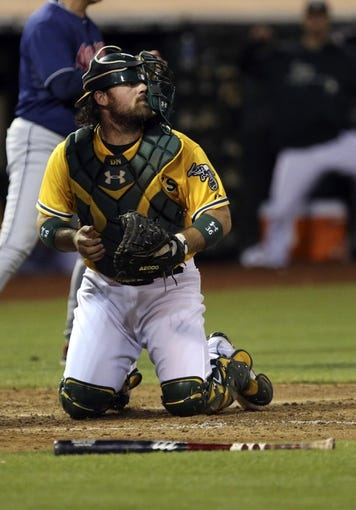 Aug 17, 2013; Oakland, CA, USA; The mask of Oakland Athletics catcher Derek Norris (36) is knocked sideways after Cleveland Indians right fielder Drew Stubbs (not pictured) slid home for a run during the ninth inning at O.co Coliseum. The Cleveland Indians defeated the Oakland Athletics 7-1. Mandatory Credit: Kelley L Cox-USA TODAY Sports