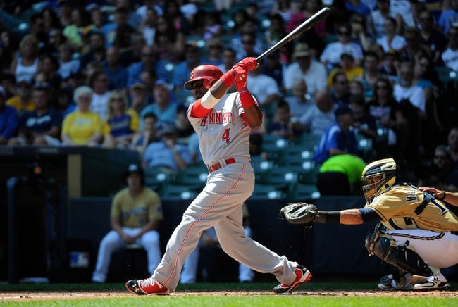 Aug 18, 2013; Milwaukee, WI, USA;  Cincinnati Reds second baseman Brandon Phillips (left) hits a double to drive in two runs in the second inning against the Milwaukee Brewers at Miller Park. At right is Milwaukee Brewers catcher Martin Maldonado.  Mandatory Credit: Benny Sieu-USA TODAY Sports