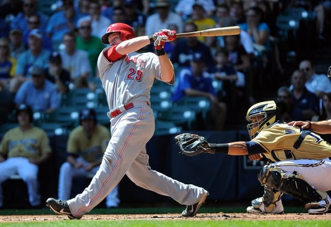 Aug 18, 2013; Milwaukee, WI, USA;  Cincinnati Reds catcher Ryan Hanigan (left) hits a single to drive in two runs in the second inning against the Milwaukee Brewers at Miller Park.   At right is Milwaukee Brewers catcher Martin Maldonado.  Mandatory Credit: Benny Sieu-USA TODAY Sports