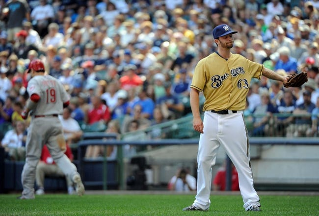 Aug 18, 2013; Milwaukee, WI, USA; Milwaukee Brewers pitcher Tyler Thornburg (right) reacts after walking Cincinnati Reds first baseman Joey Votto (left) to force in a run in the fifth inning at Miller Park. Mandatory Credit: Benny Sieu-USA TODAY Sports