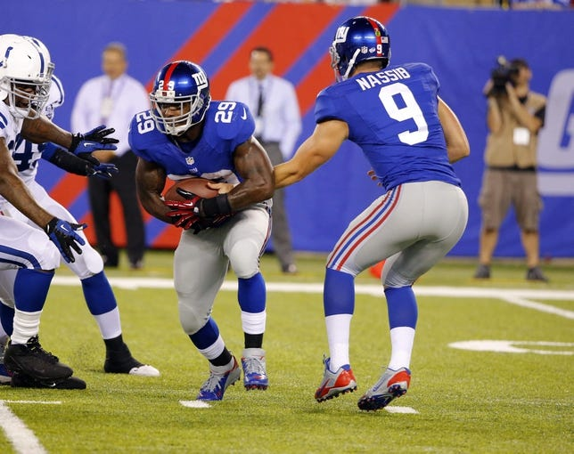 Aug 18, 2013; East Rutherford, NJ, USA; New York Giants quarterback Ryan Nassib (9) hands the ball off to running back Michael Cox (29) during the second half against the Indianapolis Colts at MetLife Stadium. Indianapolis Colts defeat the New York Giants 20-12. Mandatory Credit: Jim O'Connor-USA TODAY Sports