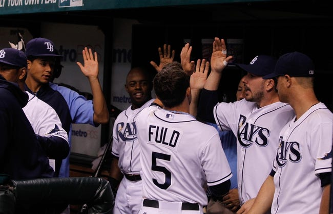 Aug 15, 2013; St. Petersburg, FL, USA; Tampa Bay Rays left fielder Sam Fuld (5) is congratulated by teammates in the dugout after he scored during the fifth inning against the Seattle Mariners at Tropicana Field. Mandatory Credit: Kim Klement-USA TODAY Sports