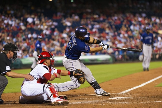 Aug 19, 2013; Philadelphia, PA, USA; Colorado Rockies catcher Wilin Rosario (20) hits a two run single during the eighth inning against the Philadelphia Phillies at Citizens Bank Park. The Phillies defeated the Rockies 5-4. Mandatory Credit: Howard Smith-USA TODAY Sports