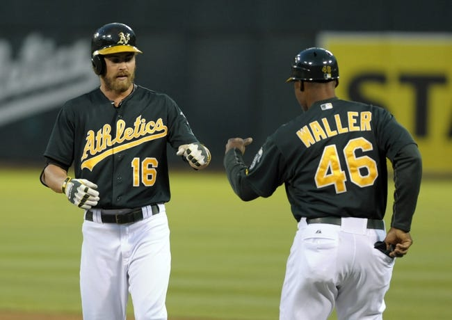 Aug 19, 2013; Oakland, CA, USA; Oakland Athletics first base coach Tye Waller (46) congratulates right fielder Josh Reddick (16) after he hit a single during the fourth inning of the game against the Seattle Mariners at O.Co Coliseum. Mandatory Credit: Ed Szczepanski-USA TODAY Sports
