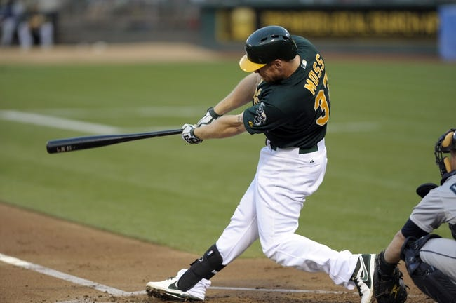 Aug 19, 2013; Oakland, CA, USA; Oakland Athletics first baseman Brandon Moss (37) hits a single against the Seattle Mariners during the second inning at O.Co Coliseum. Mandatory Credit: Ed Szczepanski-USA TODAY Sports