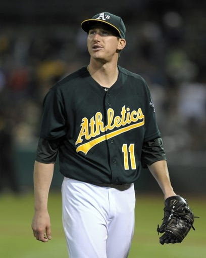 Aug 19, 2013; Oakland, CA, USA; Oakland Athletics starting pitcher Jarrod Parker (11) walks off the mound during the eighth inning of the game against the Seattle Mariners at O.Co Coliseum. The Oakland Athletics defeated the Seattle Mariners 2-1. Mandatory Credit: Ed Szczepanski-USA TODAY Sports