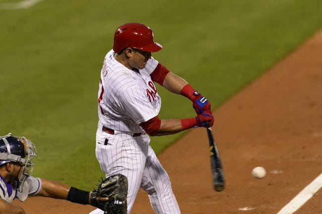 Aug 20, 2013; Philadelphia, PA, USA; Philadelphia Phillies catcher Carlos Ruiz (51) puts the ball in play during the third inning against the Colorado Rockies at Citizens Bank Park. Mandatory Credit: Howard Smith-USA TODAY Sports