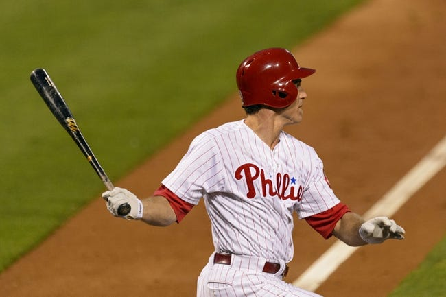 Aug 20, 2013; Philadelphia, PA, USA; Philadelphia Phillies second baseman Chase Utley (26) hits an RBI single during the third inning against the Colorado Rockies at Citizens Bank Park. Mandatory Credit: Howard Smith-USA TODAY Sports