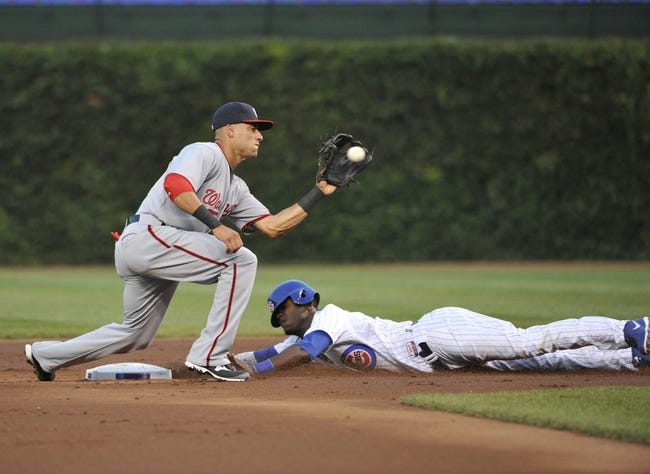 Aug 20, 2013; Chicago, IL, USA; Chicago Cubs left fielder Junior Lake (21) steals second base as Washington Nationals shortstop Ian Desmond (20) takes the throw during the first inning at Wrigley Field. Mandatory Credit: David Banks-USA TODAY Sports