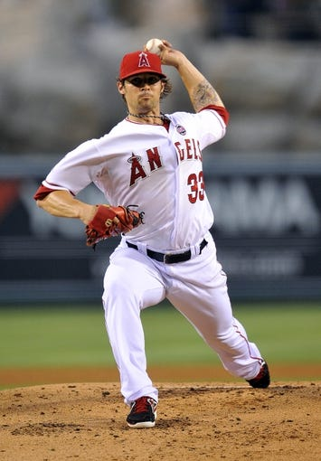 August 20, 2013; Anaheim, CA, USA; Los Angeles Angels starting pitcher C.J. Wilson (33) pitches during the second inning against the Cleveland Indians at Angel Stadium of Anaheim. Mandatory Credit: Gary A. Vasquez-USA TODAY Sports