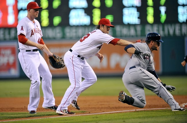 August 20, 2013; Anaheim, CA, USA; Los Angeles Angels starting pitcher C.J. Wilson (33) tags out Cleveland Indians catcher Yan Gomes (10) at first in the second inning at Angel Stadium of Anaheim. Mandatory Credit: Gary A. Vasquez-USA TODAY Sports