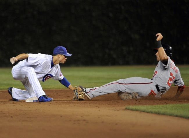 Aug 20, 2013; Chicago, IL, USA; Chicago Cubs second baseman Darwin Barney (15) tags out Washington Nationals shortstop Ian Desmond (20) on a steal attempt of second base during the ninth inning at Wrigley Field. Mandatory Credit: David Banks-USA TODAY Sports
