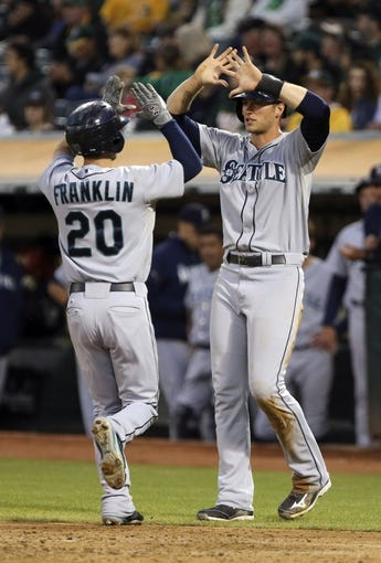 Aug 20, 2013; Oakland, CA, USA; Seattle Mariners center fielder Michael Saunders (55) waits at home plate to high five second baseman Nick Franklin (20) after his two run home run to bat in Miller against the Oakland Athletics during the third inning at O.co Coliseum. Mandatory Credit: Kelley L Cox-USA TODAY Sports