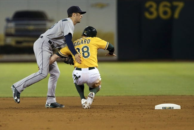 Aug 20, 2013; Oakland, CA, USA; Oakland Athletics shortstop Eric Sogard (28) collides into Seattle Mariners second baseman Nick Franklin (20) as Franklin turns the double play during the fourth inning at O.co Coliseum. Mandatory Credit: Kelley L Cox-USA TODAY Sports