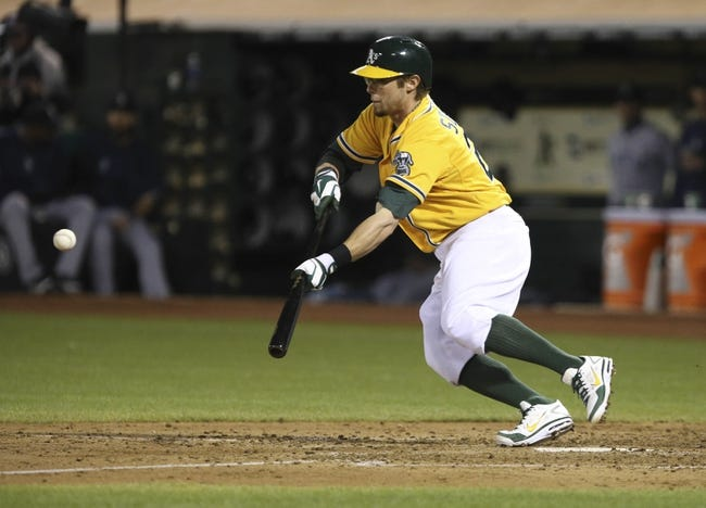 Aug 20, 2013; Oakland, CA, USA; Oakland Athletics shortstop Eric Sogard (28) bunts the ball for a single against the Seattle Mariners during the fourth inning at O.co Coliseum. Mandatory Credit: Kelley L Cox-USA TODAY Sports