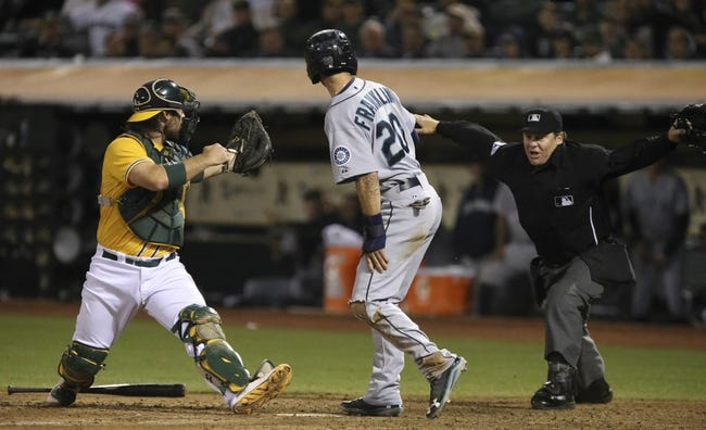 Aug 20, 2013; Oakland, CA, USA; Oakland Athletics catcher Derek Norris (36) reacts as home plate umpire Paul Schrieber (43) calls Seattle Mariners second baseman Nick Franklin (20) safe for a run during the eighth inning at O.co Coliseum. The Seattle Mariners defeated the Oakland Athletics 7-4. Mandatory Credit: Kelley L Cox-USA TODAY Sports