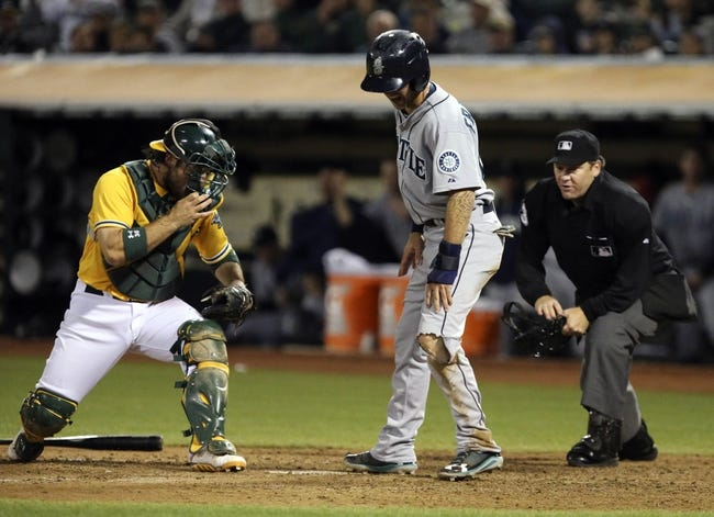Aug 20, 2013; Oakland, CA, USA; Seattle Mariners second baseman Nick Franklin (20) tears his pants on a slide for a run against Oakland Athletics catcher Derek Norris (36) during the eighth inning at O.co Coliseum. The Seattle Mariners defeated the Oakland Athletics 7-4. Mandatory Credit: Kelley L Cox-USA TODAY Sports