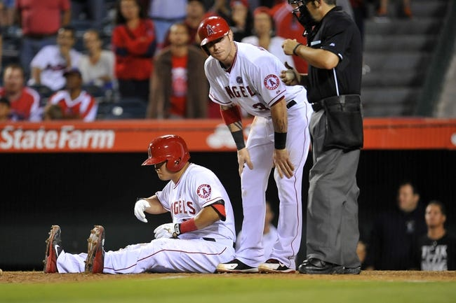 August 20, 2013; Anaheim, CA, USA; Los Angeles Angels right fielder Josh Hamilton (32) comes to catcher Hank Conger (16) after he avoids an inside pitch in the tenth inning against the Cleveland Indians at Angel Stadium of Anaheim. Mandatory Credit: Gary A. Vasquez-USA TODAY Sports