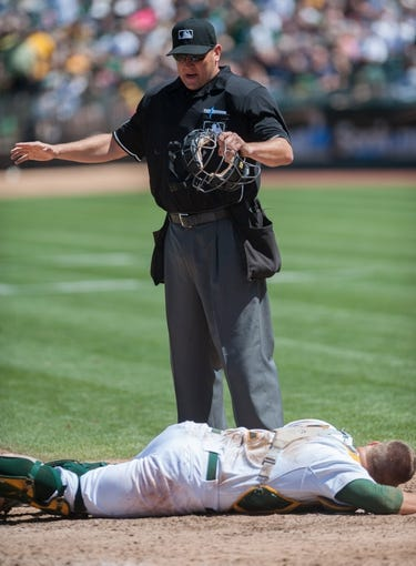 Aug 21, 2013; Oakland, CA, USA; Home plate umpire Chad Fairchild (75) calls Seattle Mariners second baseman Dustin Ackley (13, not pictured) safe after colliding with Oakland Athletics catcher Stephen Vogt (21) during the sixth inning at O.Co Coliseum. Mandatory Credit: Ed Szczepanski-USA TODAY Sports