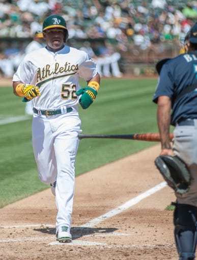 Aug 21, 2013; Oakland, CA, USA; Oakland Athletics left fielder Yoenis Cespedes (52) scores against the Seattle Mariners during the fourth inning at O.Co Coliseum. Mandatory Credit: Ed Szczepanski-USA TODAY Sports