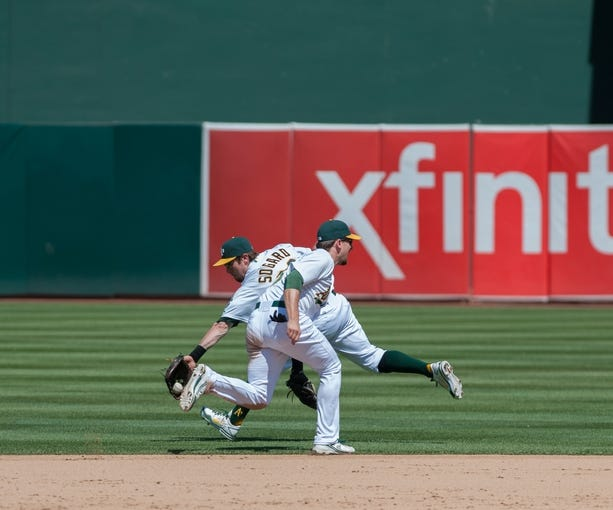 Aug 21, 2013; Oakland, CA, USA; Oakland Athletics second baseman Eric Sogard (28) fields a ground ball past shortstop Jed Lowrie (8) during the eighth inning at O.Co Coliseum. The Seattle Mariners defeated the Oakland Athletics 5-3. Mandatory Credit: Ed Szczepanski-USA TODAY Sports